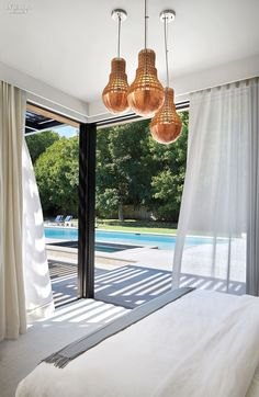ICrave Fashions a Private Garden of Eden with a Backyard Pavilion and Accompanying Lap Pool | Brass pendant fixtures hang in the bedroom. #design #interiordesign #interiordesignmagazine #projects #countryhouses