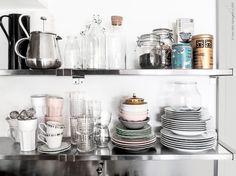 Hemma i Fridas kök: Rostfria hyllplanen EKBY MOSSBY med EKBY BJÄRNUM konsoller, BEHÖVD termoskanna, ANRIK te/kaffepress, ENSIDIG vas/flaska, KORKEN glasflaskor och burkar. TILLBAKA, POKAL och MATSEDEL muggar. FRASERA, IVRIG och VAKEN glas. Porslin ur serierna IKEA 365+, POKAL, ARV och FRODIG.