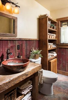 Builder Greg Lee used red reclaimed barn wood as wainscoting. He also built the vanity and corner cabinet out of reclaimed barn wood. For the sink, Mikki requested that Whitefish Pottery create an 18-inch vessel that matched the red reclaimed barn wood. A ceramic tile floor with radiant heating completes the look.