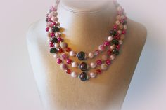 Chunky glass beaded triple strand necklace. In various shades of hot pink, light pink and purple.