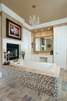 The glass tile on the tub skirt creates a focal point for the over size square bathtub and beautiful marble tub deck.