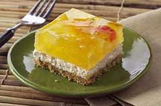 Tropical Layered Dessert - graham cracker and coconut crust is topped with cream cheese and pineapple gelatin laced with fruit cocktail for a luscious chilled dessert.