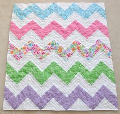 This summery zig zag quilt with flowers and polka dots measures 34.5x38. The colors are hot and light pink, green, bright blue, purple, and orange, with just a wee bit of yellow in the flowers, and white. The back is a light pink gingham.  It is hand tied in the patterned zig zags, and hand stitched in the white zig zags with white embroidery floss. It has been hand washed and damp dried and is very crinkly and cozy.