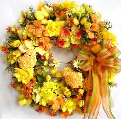 """This beautiful Spring, Easter Orange/Yellow flower door wreath sets on a green styrofoam wreath base.    The wreath is embellished with beautiful orange/yellow daisies, orange alstroemerias, yellow and orange hydrangea,tulips, and roses. The wreath is accented with two lovely yellow Raz Easter Chicks and two yellow Butterflies . I finished the wreath with an orange/yellow/light green ribbon bow.     The wreath measures from tip to tip at 24"""" (L) x 24"""" (W) x 7""""(D)."""