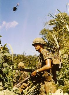 A Radio Telephone Operator (RTO)of the 101st Airborne on patrol near Mai Loc, twelve miles from the DMZ.    A Light Observation Helicopter (Loach) of the 17th Cavalry flies overhead.    Photo taken: October 1969.