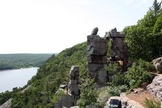 Hikers wait to take photos under Devil's Doorway, a rock formation on the East Bluff at Devil's Lake State Park.