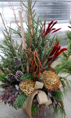 Group complimentary colors of dyed natural elements (grass and eucalyptus) along with dried hydrangea, cones, curly willow gathered in a circle and a burlap bow for this decorated spruce top pot