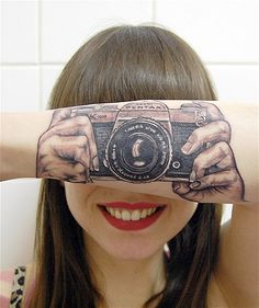 Photography aficionado Lotte van den Acker, 24, of Brunssum, Netherlands, sports a tattoo of a vintage 1970s Asahi Pentax 35mm SLR on her arm. Lotte started using a Pentax camera at age 10, said her mother, Helma, who applied the tattoo. (© Helma van der Weide/Rex Features)