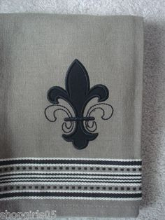 NEW! BEAUTIFUL FLEUR DE LIS KITCHEN TOWEL WOULD LOOK GREAT IN YOUR HOME. THEY ARE A GREAT GIFT IDEA ALSO.  COLORS ARE TAUPE, BLACK AND WHITE. MEASURES APPROX. 18 X 28 INCHES. REALLY CUTE!!