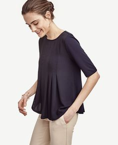 "Pretty pleats add a hint of swing to this refined matte jersey top. Boatneck. Short sleeves. 24 3/4"" long."