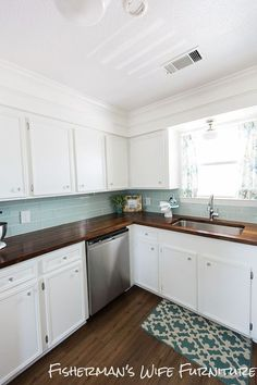 Blue sea glass backsplash creates a fun pop of color in this white kitchen with custom butcher block countertops