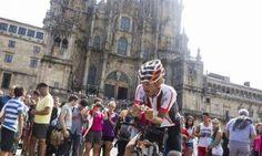 Mikel Azparren, en su bicicleta con la catedral a su espalda y turistas observándolo ayer. // Óscar Corral