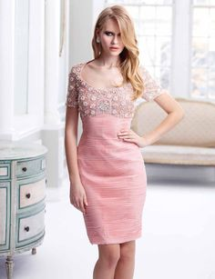 Terani Couture Cocktail C1711  Short sleeve cocktail dress with empire bust line and scoop neckline. Top is adorned with intricate beadwork and segues into a horizontally pleated skirt that falls above the knee.
