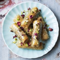 baklava rolls, served with honey syrup and scattered with pistachios and delicate rose petals.