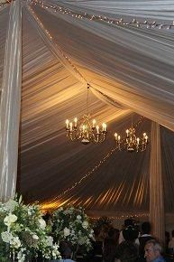 chandeliers and fairy lights in a draped tent <3