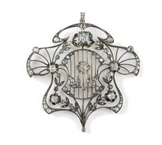A Diamond, Gold and Platinum Pendant, St. Petersburg, 1908-1917. The shaped openwork pendant in Art Nouveau style, centering a grille supporting a diamond-set flowerhead and leaves, surrounded by diamond-set flowers.
