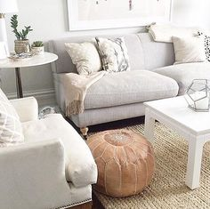 Grey couches, leather pouf, marble side tables