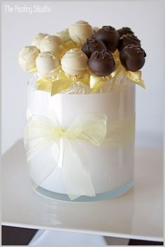 This would be a cute centerpiece, though I can't imagine how many pops I would have to make! Maybe I could find a larger glass vase or square bowl to put all the cake pops in as a favor that way I can put a burgundy ribbon around it!