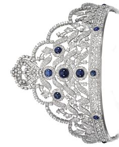 SAPPHIRE AND DIAMOND TIARA. Designed as graduating open work foliate scroll motifs set with brilliant-, circular-, single- and step-cut diamonds, highlighted at the centre with cabochon sapphires, circumference approximately 135mm, fitted case.