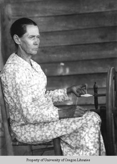 A Doris Ulmann photograph of Mary Willmott, a spinner, weaver and quilter in Berea, Kentucky. The photograph was probably taken in the early 1930's.     Mrs. Willmott is winding yarn onto the spindle shaft, but I cannot see the tip of the spindle.    Any ideas? How was she spinning her yarn if there is no tip to the shaft of the spindle?