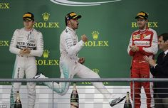 Hamilton jumps for joy  in front of second-placed Mercedes team-mate Nico Rosberg and Ferrari's Sebastian Vettel who finished third