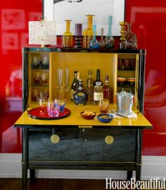 In a colorful and small Manhattan apartment designed by Philip Gorrivan, a vintage bar cabinet by De Coene Frères is as glossy as the walls, which are lacquered in a custom red from Fine Paints of Europe. It makes entertaining easy.