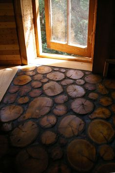 """Real wood log slices are sealed and embedded into a base to make this wonderful rustic """"wood tile"""" floor"""