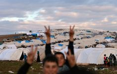 SYRIA, ATME : Displaced Syrian refugees flash the victory sign at the refugee camp of Qah along the Turkish border in the village of Atme in the northwestern province of Idlib, on January 31 2012. AFP PHOTO/AAMIR QURESHI