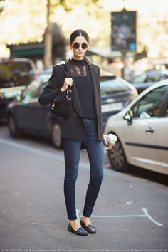Cecilia in black sweater, blazer, blue jeans, and studded black loafers.
