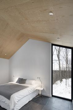 The bedroom's vertical, floor-to-ceiling window lets occupants admire the graceful trees outside. A Mini Tolomeo lamp by Artemide sits on the bedside table.