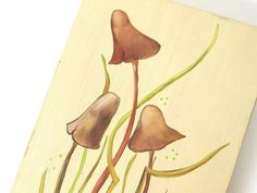 This vintage wall hanging is so 1970s! With earth tone shades of rust, brown and green, these hand painted, funky fungi mushrooms have a soft yellowish green background. This art plaque picture would add a bit of retro style to your wall! There is a hanger on the back. Sides are similar in color to tallest mushroom  It is 4 7/8 inches (12.4 cm) across, 7 3/8 inches (18.8 cm) tall and 5/8 inch (1.6 cm) deep. Sides are slightly beveled, so front is slightly smaller than back.  It is in…