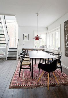 Dining table with mixed chairs (Eames, Wishbone), Kelim rug and Poulsen lamp