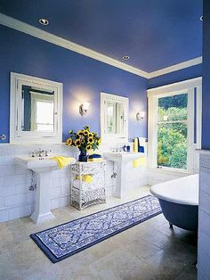 The two pedestal sinks in this remodeled 1908 bathroom leave most of the new limestone floor exposed, accentuating the room's volume. The 8-foot-wide room retains the original medicine cabinets and claw-foot tub. Formal white molding contrasts vividly with rich azure walls. (Photo: Photo: David Wakely; Designer: Brad Polvorosa)
