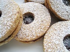 Linzer Sables (Dorie Greenspan)  1 1/2 cups finely ground almonds, hazelnuts, or walnuts  1 1/2 cups all-purpose flour  1 1/2 teaspoons ground cinnamon  1/4 teaspoon salt  scant 1/4 teaspoon ground cloves  1 large egg  2 teaspoons water  1 stick (8 tablespoons) unsalted Butter, at room temperature  1/2 cup sugar  1/2 cup raspberry jam or strained apricot jam plus 1 teaspoon water