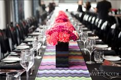 Missoni inspired table runner with pink floral arrangements + black vases.