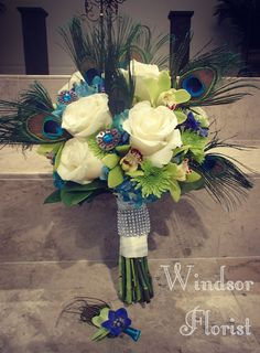 BRIDAL BOUQUET : Beautiful Peacock tinted Hydrangeas, Accented with Peacock feathers , gems, fragrant Ivory Roses, green cymbidium orchids, lime button mums, and blue delphinium, hand tied with Rhinestones. BOUTONNIERE : Lime dendrobium orchid, blue delphinium bloom. accented with peacock feather and teal ribbon