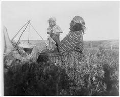 Nitana рядом с треногой держит ребёнка. Черноногие, период 1905 года.