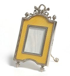 Fabergé silver frame, workmaster Johann Viktor Aarne, St. Petersburg, pre 1896. In the Louis XVI taste, decorated with translucent yellow enamel over a dappled engraved ground, the curved pediment, surmounted by a laurel crowned trophy of crossed quivers and two flaming torches, emblematic of the Triumph of Love. Purchased jointly by Grand Dukes George and Michael Alexandrovich in 1897 for 140 roubles.