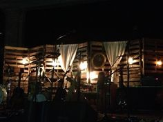 Perfect thing to do with pallets! Add some lighting, curtains, and decor and it is perfect for an outdoor space, wedding, or as it is here - backdrop for a David Crowder concert!