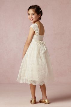 The Elsie Flower Girl Dress by BHLDN  Crafted of delicate lace, this vintage-inspired dress features scallops at the hem, light smocking at the back, and ribbon ties to finish off the little lady's look with a sweet bow. Back ties. Silk, cotton, nylon lace; polyester lining
