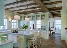 This farmhouse kitchen by Donald Lococo Architects is a luscious faded green, with a wonderful flow, fabulous storage and a pass through to connect the work space with the dining space.