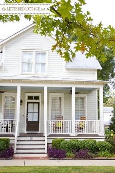 white farmhouse with porch- The body color is called Distant Mountain. It's a very pale blue/green/gray. The trim and underskirt color is a creamy off-white called Cameo. The front door color is Artisan Brown. They're all Glidden colors.