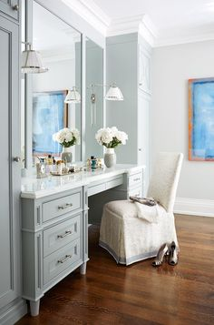 The master bedroom's graceful dressing area is painted in Sherwin Williams's Repose Gray. The sconces are by Galerie des Lampes, and the slipper chair is covered in a fabric by Thom Filicia for Kravet and accented with a Samuel & Sons trim.