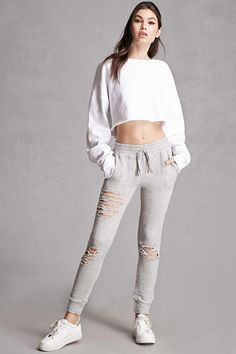A pair of heathered knit joggers featuring a distressed design, elasticized drawstring waist, a French terry cloth lining, two front slanted pockets, and cuffed ankles. This is an independent brand and not a Forever 21 branded item.