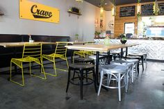 Crave 443– Adelaide   Concept Collections   Oscar chair in yellow, Classique stools in black and silver and banquet seating allong the wall.