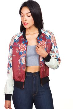 Exotic floral print bomber jacket with a round neck line. Solid ribbed contrast along the edges and zipper down the front center. Statement jacket for any casual day out. *Hand Wash Cold and Lay Flat