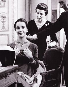 Elizabeth Taylor being attended by Louise Arpels at the Van Cleef & Arpels' Place Vendome salon. A pleased diva.