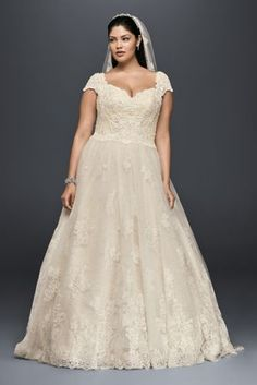 This lovely cap sleeve ball gown is the perfect combination of grand and soft. Embellished with beading and lace appliques, the gown\'s soft volume and fluid movement is created by over 35 yards of tu
