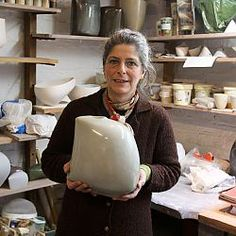 Ruth King holding her pale blue/grey salt glazed soft pot.