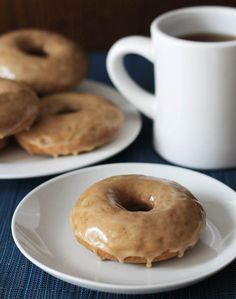 A plate of Vegan Gluten Free Maple Doughnuts sits in the background, in the foreground, one doughnut sits on a small white plate, a cup of black coffee is on the right in the background.